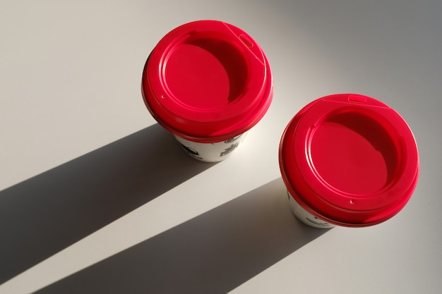 2 paper cup boxes with a red lid are on the table in the cafe. coffee to go. morning.