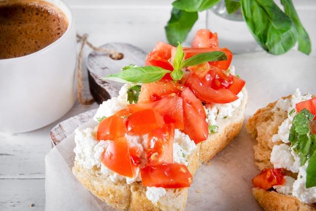 白い木の表面に、ソフトチーズ、トマトスライス、バジル、ブラックコーヒー1杯のサンドイッチ2枚、朝食、