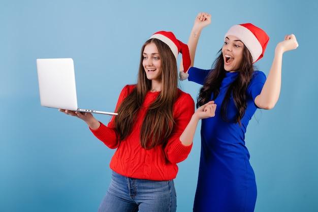 2 усмехаясь женщины нося шляпы santa смотря компьтер-книжку с счастливыми жестами изолированную над синью