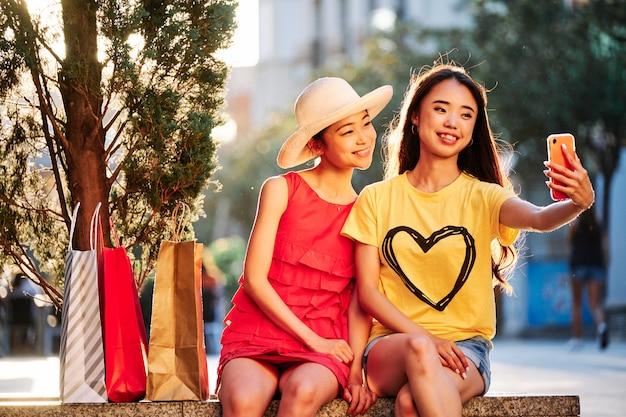 2 азиатских женщины ходя по магазинам и принимая selfie outdoors