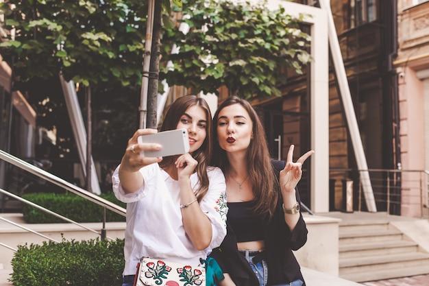 2人の面白い女の子は、selfieを取ります。友人が街でselfieを取る