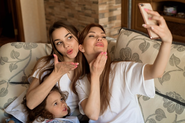 2人の若い女の子と自宅のソファの上の少女のselfieの肖像画。