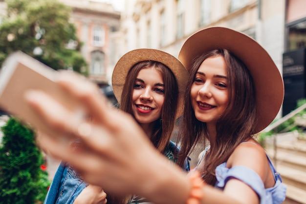 Внешний портрет 2 молодых красивых женщин принимая selfie используя телефон. девочки веселятся в городе. лучшие друзья