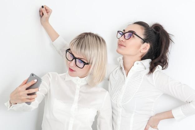白いシャツとメガネの2人の女の子が電話でselfieを行う