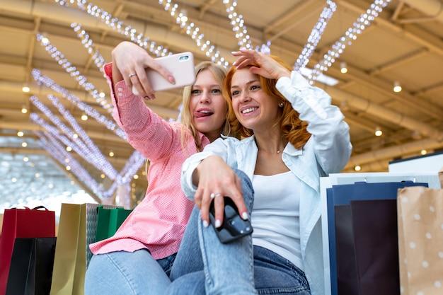 ショッピングモールで買い物をしながら2人の幸せな友人がselfieを取っています。