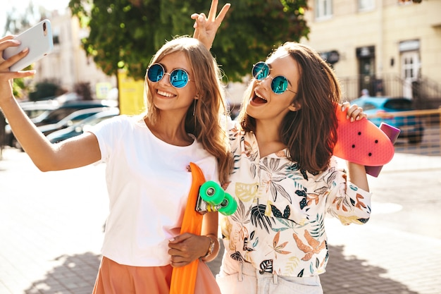 2人の若い女性のスタイリッシュなヒッピーブルネットと金髪の女性モデルは、電話でソーシャルメディアのselfie写真を撮る夏の流行に敏感な服を着ています。カラフルなペニースケートボード付き。