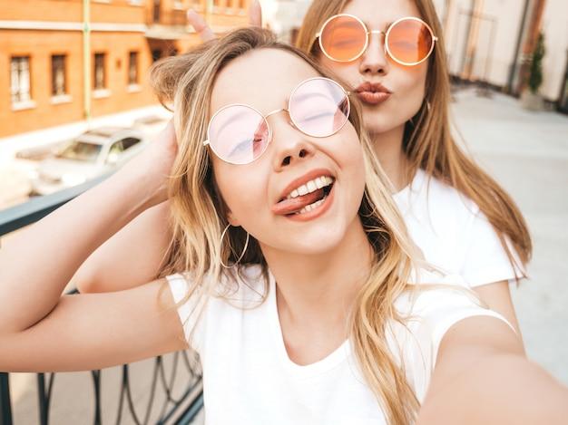2 молодых усмехаясь женщины битника белокурых в одеждах футболки лета белых. девушки, принимающие selfie автопортрет фотографий на смартфоне. ,