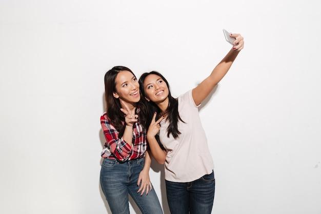 2人のアジアの陽気な肯定的な女性の姉妹はselfieを作ります