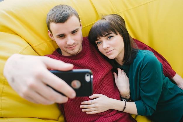 2つの笑顔の若い学生は美しいselfieを作ります。黄色の椅子のバッグの部屋の若者の肖像