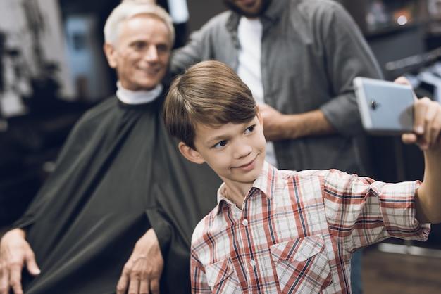 少年は2人の年上の男性と一緒にスマートフォンでselfieを作ります。