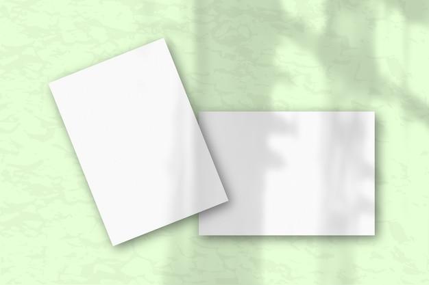 2 листа белой текстурированной бумаги на фоне серой стены. мокап с наложением тени растений. естественный свет отбрасывает тени из окна. плоская планировка, вид сверху. горизонтальная ориентация