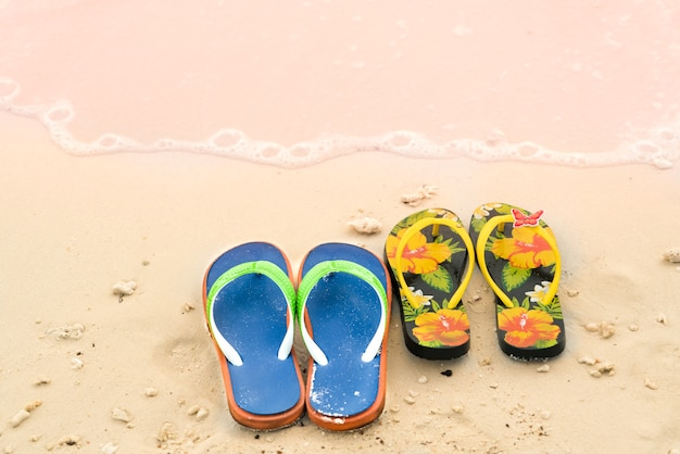 2 slippers on the white sand beach, travel and vacation time