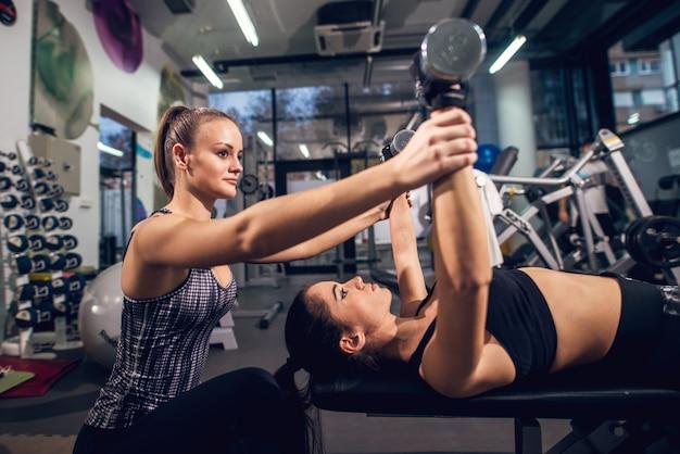Взгляд стороны близкий поднимающий вверх 2 молодых привлекательных сфокусированных sporty активных девушек пока делающ тренировки