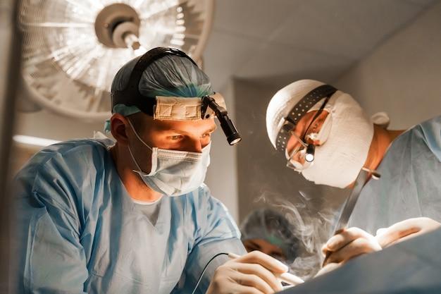 2 хирурга с налобным фонарем делают пластическую операцию в медицинской клинике. пластическая операция по увеличению груди и коррекция в медицинской клинике.
