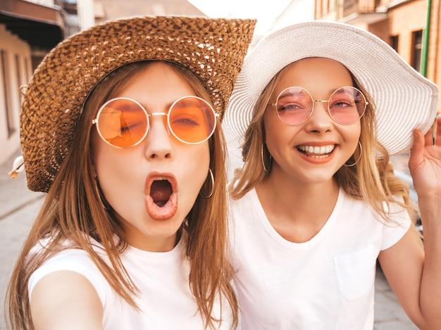夏に2人の若い笑顔ヒップスターブロンド女性白いtシャツ。スマートフォンでセルフポートレート写真を撮る女の子。通りの背景でポーズをとるモデル。女性は肯定的な感情を示しています。