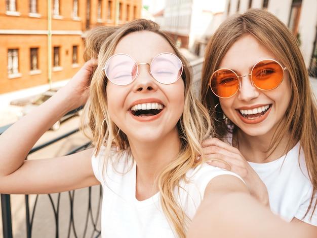 夏に2人の若い笑顔ヒップスターブロンド女性白いtシャツ服。スマートフォンでセルフポートレート写真を撮る女の子。