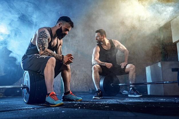 ジムでトレーニング2つの筋肉のひげを生やしたtattoed選手