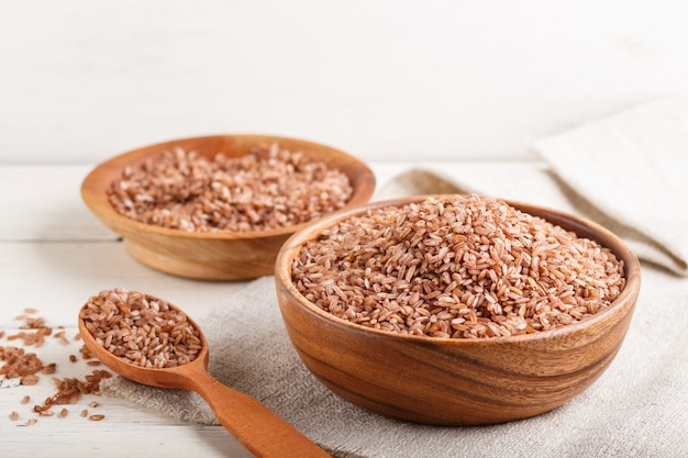 2 деревянных шара с unpolished коричневым рисом и деревянной ложкой на белой деревянной предпосылке. вид сбоку, крупным планом.