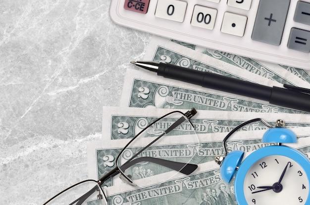 2ドル紙幣とメガネとペンで電卓。ビジネスローンや税金の支払いシーズンのコンセプト。税金を支払う時間