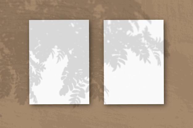 2 вертикальных листа текстурированной белой бумаги на коричневом столе