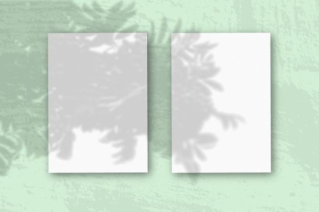 2 вертикальных листа текстурированной белой бумаги на мягком зеленом столе