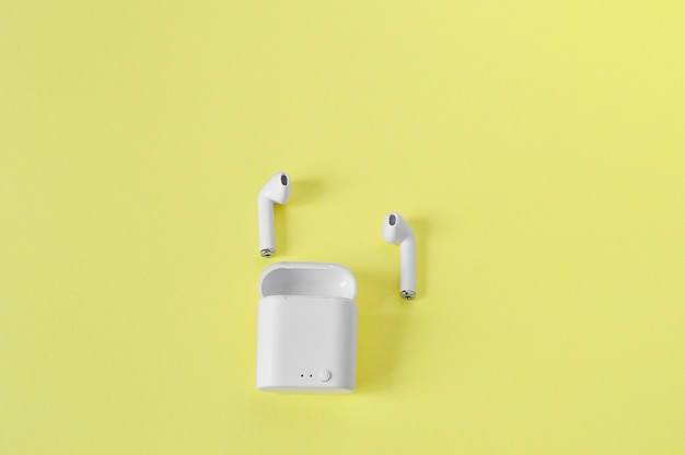 2 white wireless earphones in-ear with bluetooth on an yellow wall.copy space. flat lay.