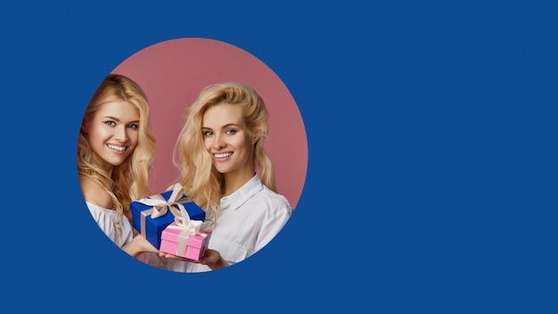 プレゼントボックスとギフトボックスを保持している2人のかわいいwomanfriens双子の女性の肖像画が壁の青い穴をのぞきます。テキスト用の空のスペース。