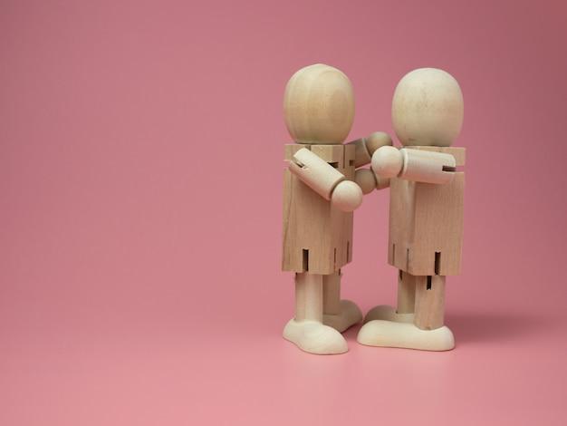 ピンクの背景でお互いをハグする2つの木製人形。木の人形からの社会的接触の概念。