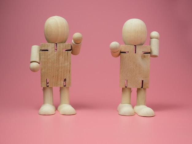 ピンク色の背景に立っている2つの木製人形の話のジェスチャー。木の人形からの社会的接触の概念。