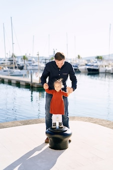 2-year old is playing with her father on a boat pier in porto montenegro.