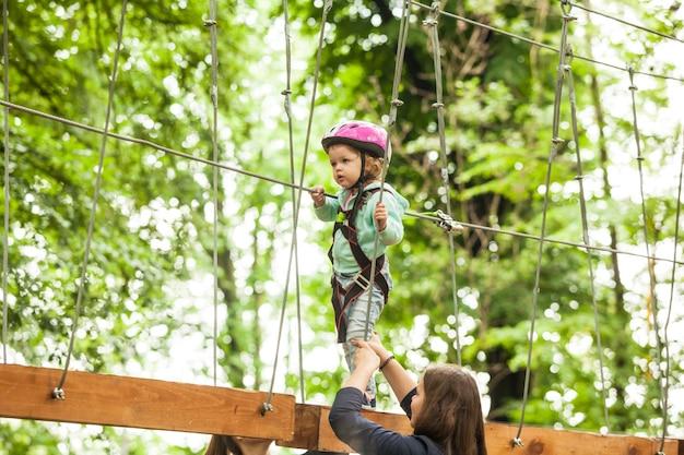 ヘルメットをかぶった2歳の少女と、アドベンチャーロープパークの安全装置。夏のレジャー