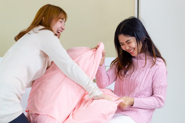 2 young women play fighting pillows