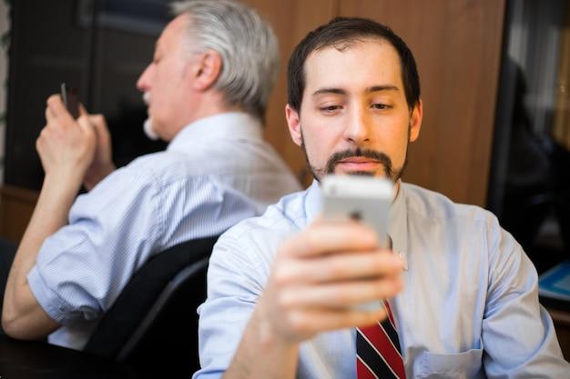 仕事の代わりに携帯電話を使用する2人の怠zyなビジネスマン