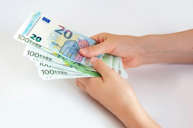 手でユーロ紙幣。孤立した白地に20と100ユーロ。保存しています。欧州連合。