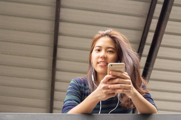 アジアの20代の10代女性の肖像画は、イヤホンで音楽を聴きます。