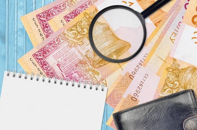 Купюры 20 белорусских рублей и увеличительное стекло с черным кошельком и блокнотом. понятие о поддельных деньгах. поиск различий в деталях денежных купюр для обнаружения фальшивых денег