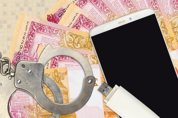 Купюры 20 белорусских рублей и смартфон в наручниках милиции. концепция хакерских фишинговых атак, незаконного мошенничества или распространения шпионского программного обеспечения в интернете