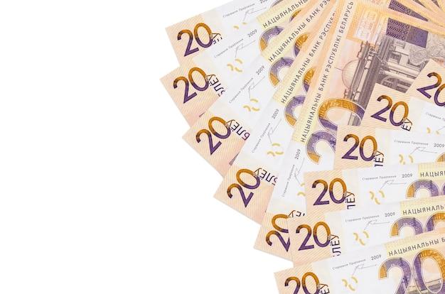 Купюры 20 белорусских рублей лежат изолированы на белой стене с копией пространства. концептуальная стена богатой жизни. большое богатство национальной валюты