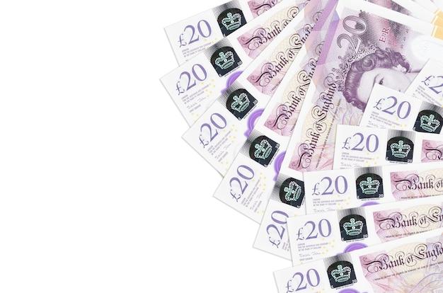 Купюры 20 британских фунтов лежат, изолированные на белом фоне с копией пространства