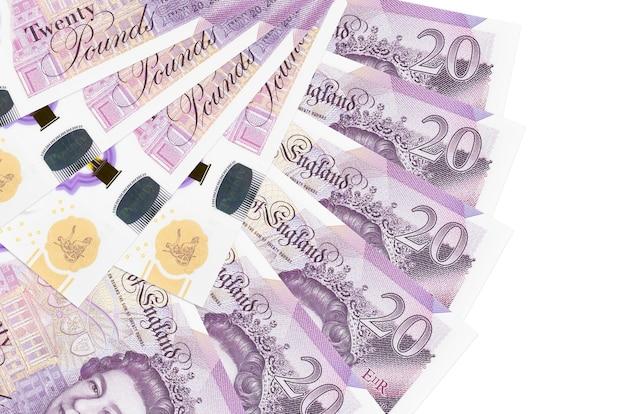 Банкноты 20 британских фунтов лежат, изолированные на белой стене с копией пространства, сложенные в форме вентилятора крупным планом. концепция финансовых операций