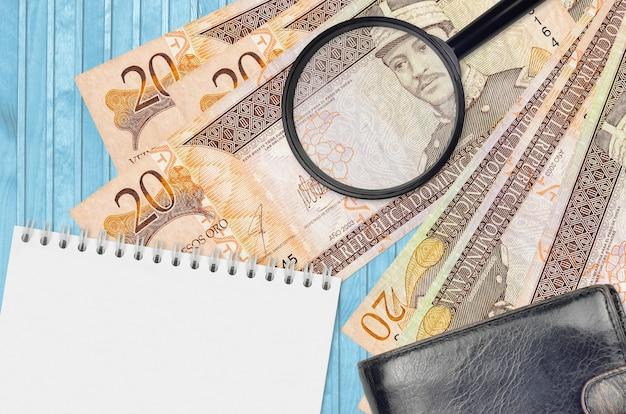 20ドミニカペソ紙幣と黒い財布付きの虫眼鏡