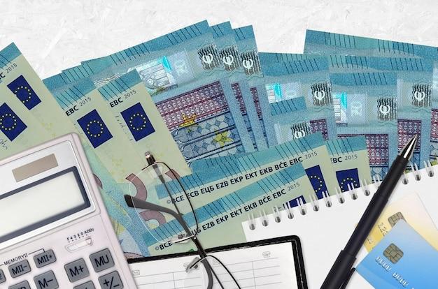 Купюры 20 евро и калькулятор с очками и ручкой. концепция уплаты налогов или инвестиционные решения. финансовое планирование или бухгалтерские документы
