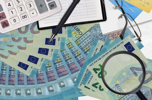 Купюры 20 евро и калькулятор с очками и ручкой