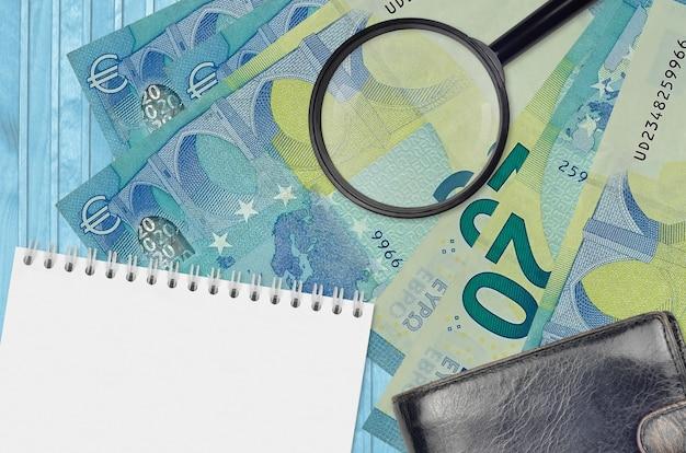 Купюры 20 евро и увеличительное стекло с черным кошельком и блокнотом. понятие о поддельных деньгах. поиск различий в деталях денежных купюр для обнаружения фальшивых денег