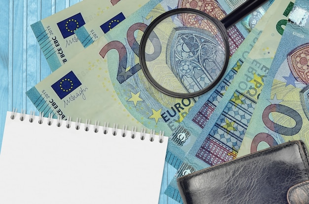 20 euro bills and magnifying glass with black purse and notepad. concept of counterfeit money. search for differences in details on money bills to detect fake money