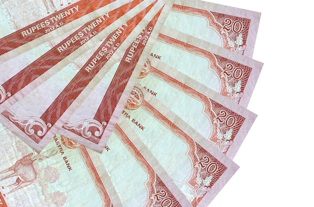 20 nepalese rupees bills lies isolated on white wall with copy space stacked in fan shape close up. financial transactions concept