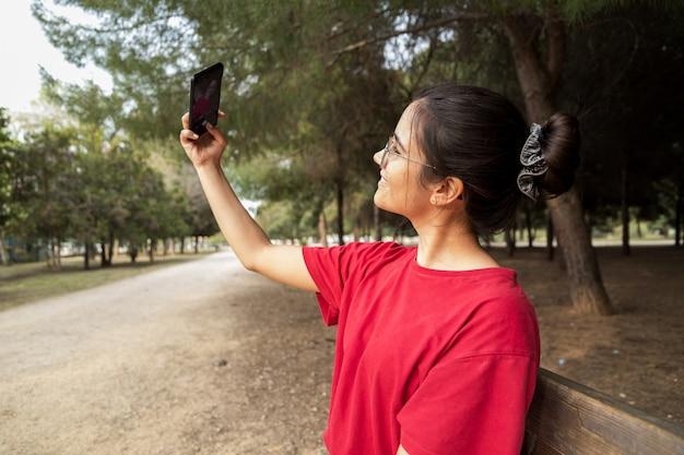 メガネと赤いシャツの20代の若い魅力的な女性は、ベンチに座って、携帯電話を持って、スペインの美しい公園で笑顔をしながら、selfieを取ります。彼女は電話を探しています