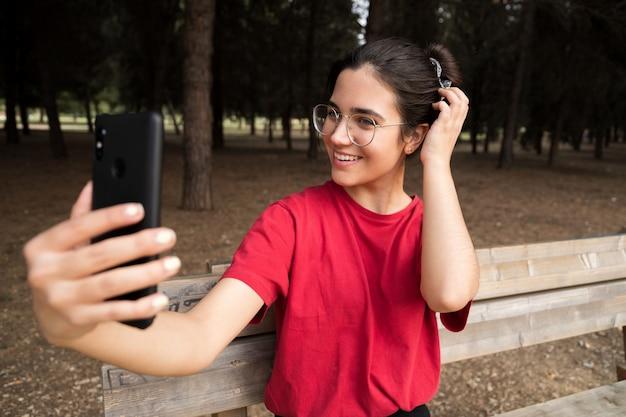 眼鏡をかけている20代の若い魅力的な女性とベンチに座っている赤いシャツ、携帯電話を押しながら美しい公園で笑顔でselfieを取っています。