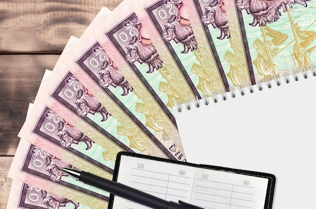 20 sri lankan rupees bills fan and notepad with contact book and black pen. concept of financial planning and business strategy