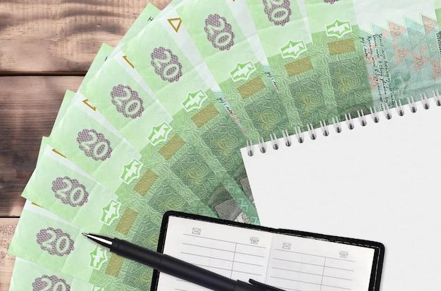 Вентилятор банкнот 20 украинских гривен и блокнот с записной книжкой и черной ручкой. концепция финансового планирования и бизнес-стратегии. бухгалтерский учет и инвестиции